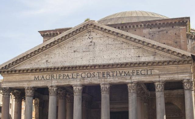 Roman style architecture: Building with Corinthian columns and text engraved on the apex facet